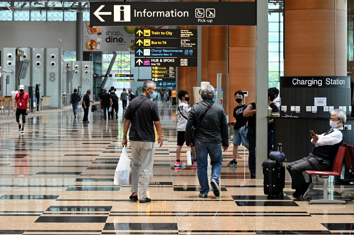 People are seen walking around the departure hall of Changi International Airport in Singapore on March 15.