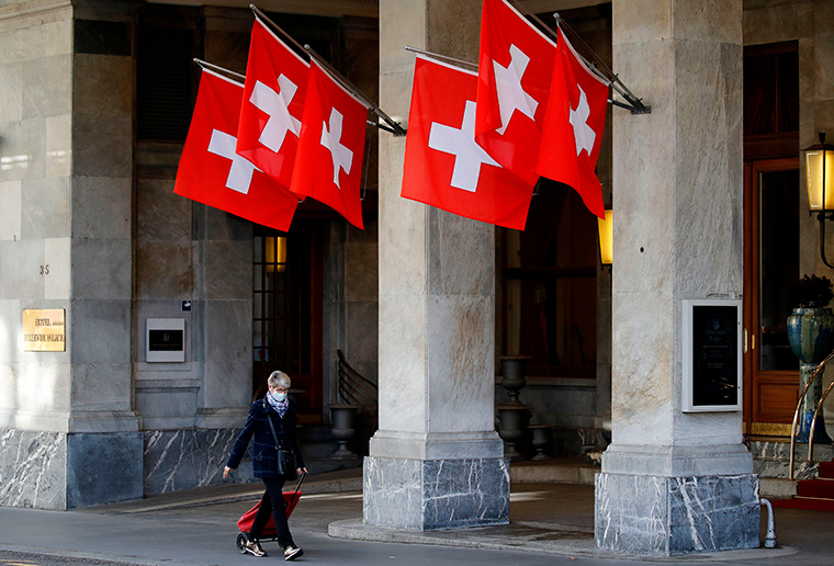 A woman walks past Swiss flags wearing a protective face mask ahead of the announcement by Swiss government of new restrictions to fight the Covid-19 outbreak in Bern, on October 27, 2020.