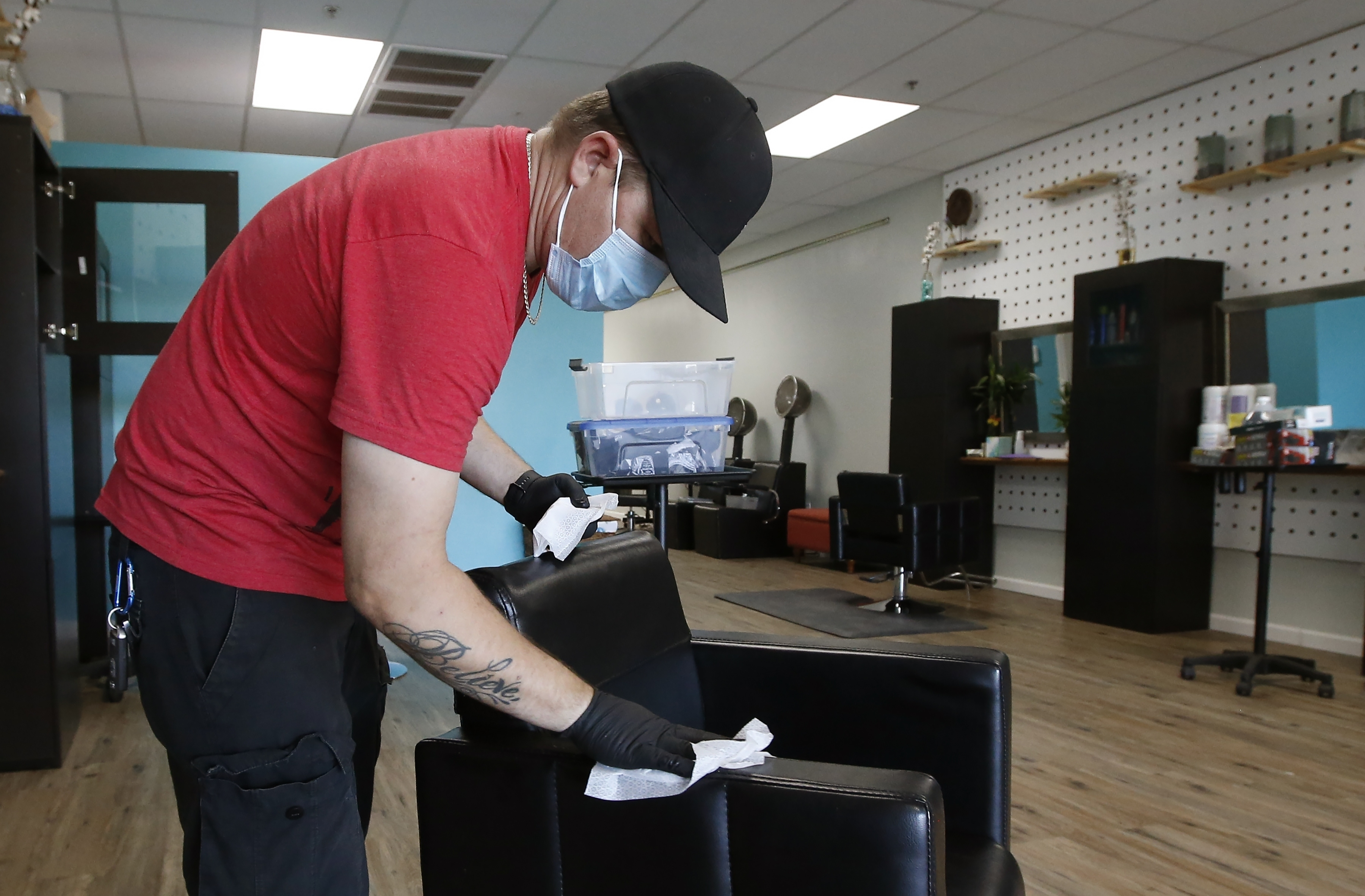Brian Waldret, co-owner of Hello Salon in Laveen, Arizona, disinfects surfaces in the salon on May 7, in preparation for reopening after being closed for several weeks due to the coronavirus.
