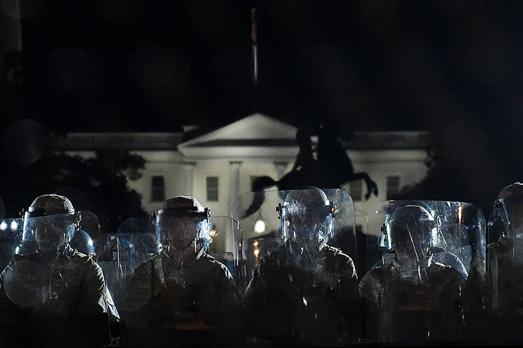 Police officers hold a perimeter behind the metal fence recently erected in front of the White House on June 2.