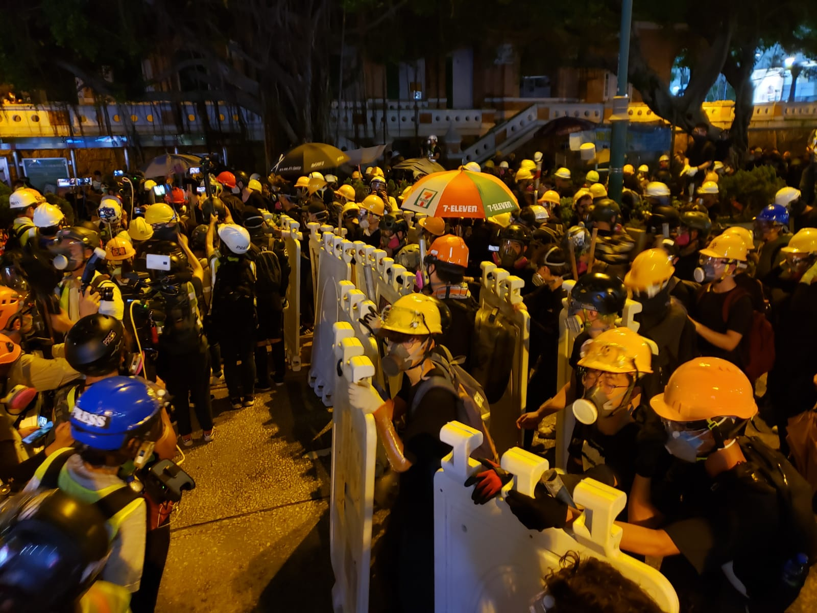 Protesters erect plastic street barriers as shields as they face off with police.