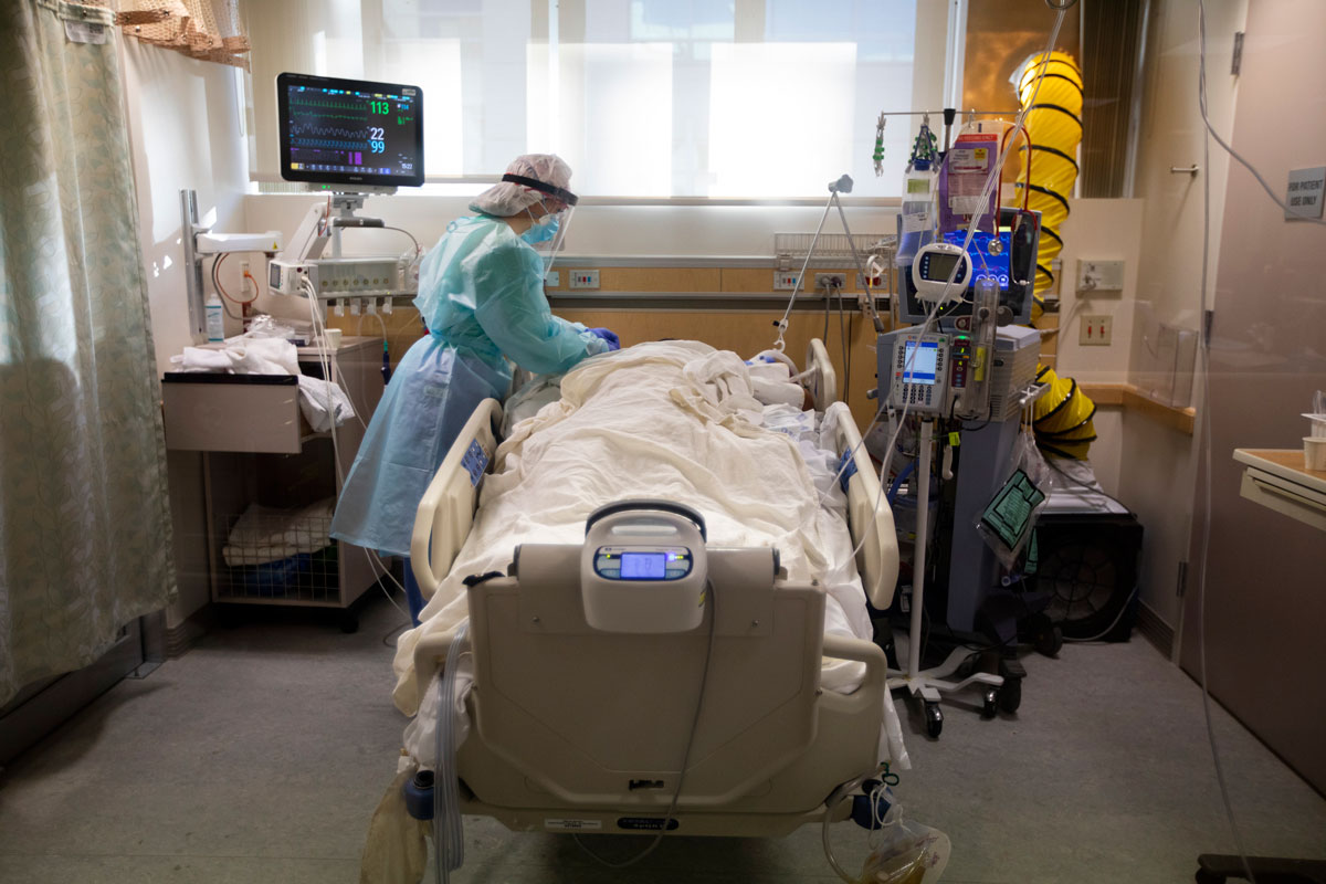 A nurse works with a Covid-positive patient inside the ICU at Providence St. Jude Medical Center on December 25 in Fullerton, California.