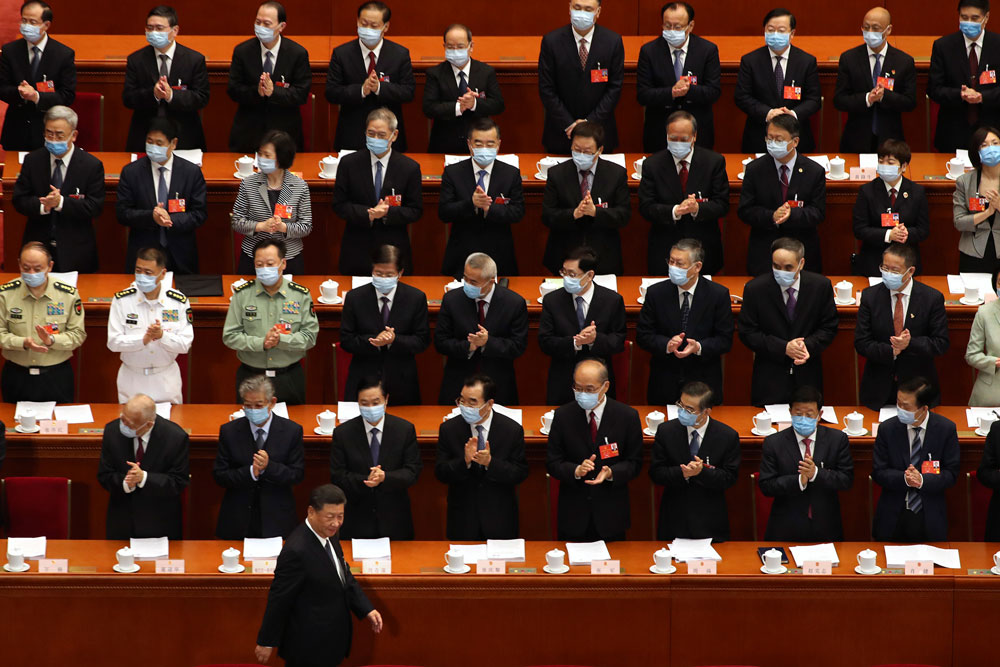 Delegates applaud as Chinese President Xi Jinping arrives for the opening session of China's National People's Congress at the Great Hall of the People in Beijing on Friday.