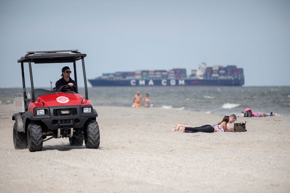 A member of the Tybee Island, Georgia, Life Guards, left, patrols the beach on an ATV while visitors sunbathe on the sand on April 4 after Gov. Brian Kemp signed an executive order allowing people to exercise outside, with social distancing of at least six feet because of the coronavirus outbreak.