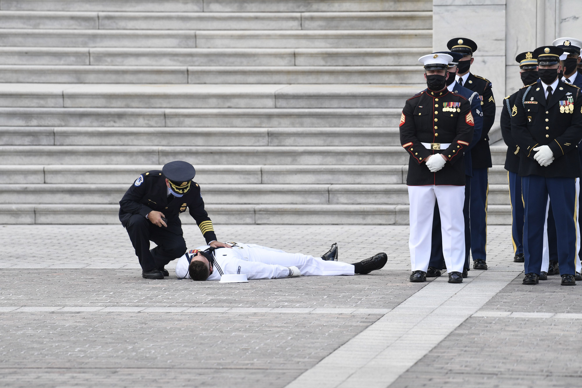 A member of a US military honor guard is checked on after collapsing in the heat of the day as a hearse carrying the casket of civil rights pioneer and longtime US Representative John Lewis arrives outside the US Capitol prior to the start of the ceremony preceding the lying in state of John Lewis in the Rotunda of the US Capitol in Washington, DC, on July 27.