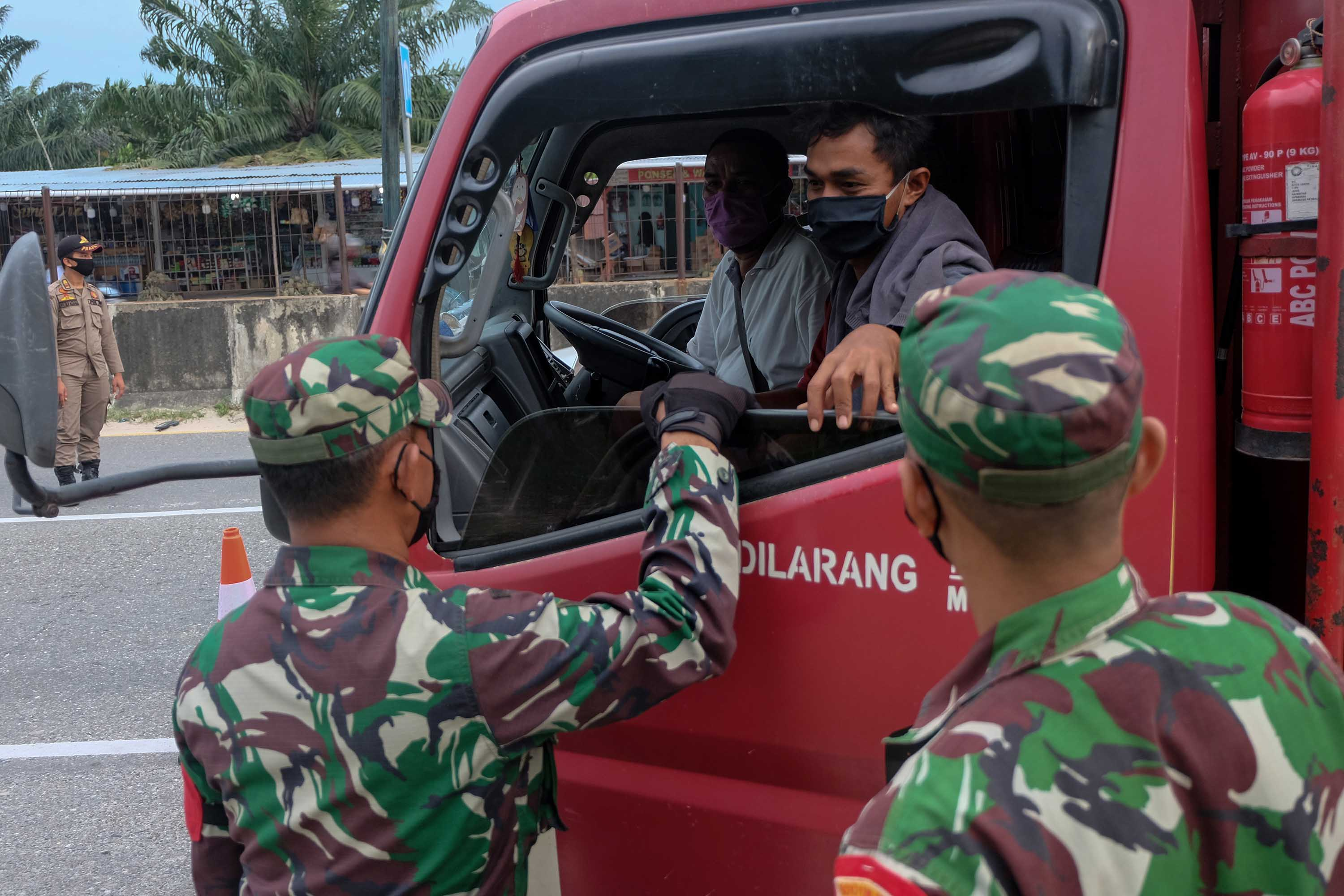 Authorities stop vehicles on a highway in Pekanbaru, Indonesia, on April 22, amid social restriction measures to curb the spread of coronavirus.