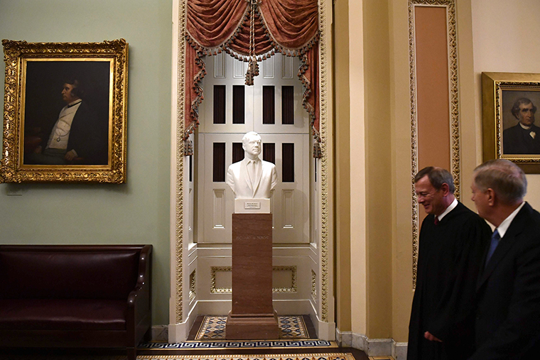 US Supreme Court Chief Justice John Roberts, left, and Senator Lindsey Graham walk past a bust of former US President Richard Nixon after the Senate impeachment vote.