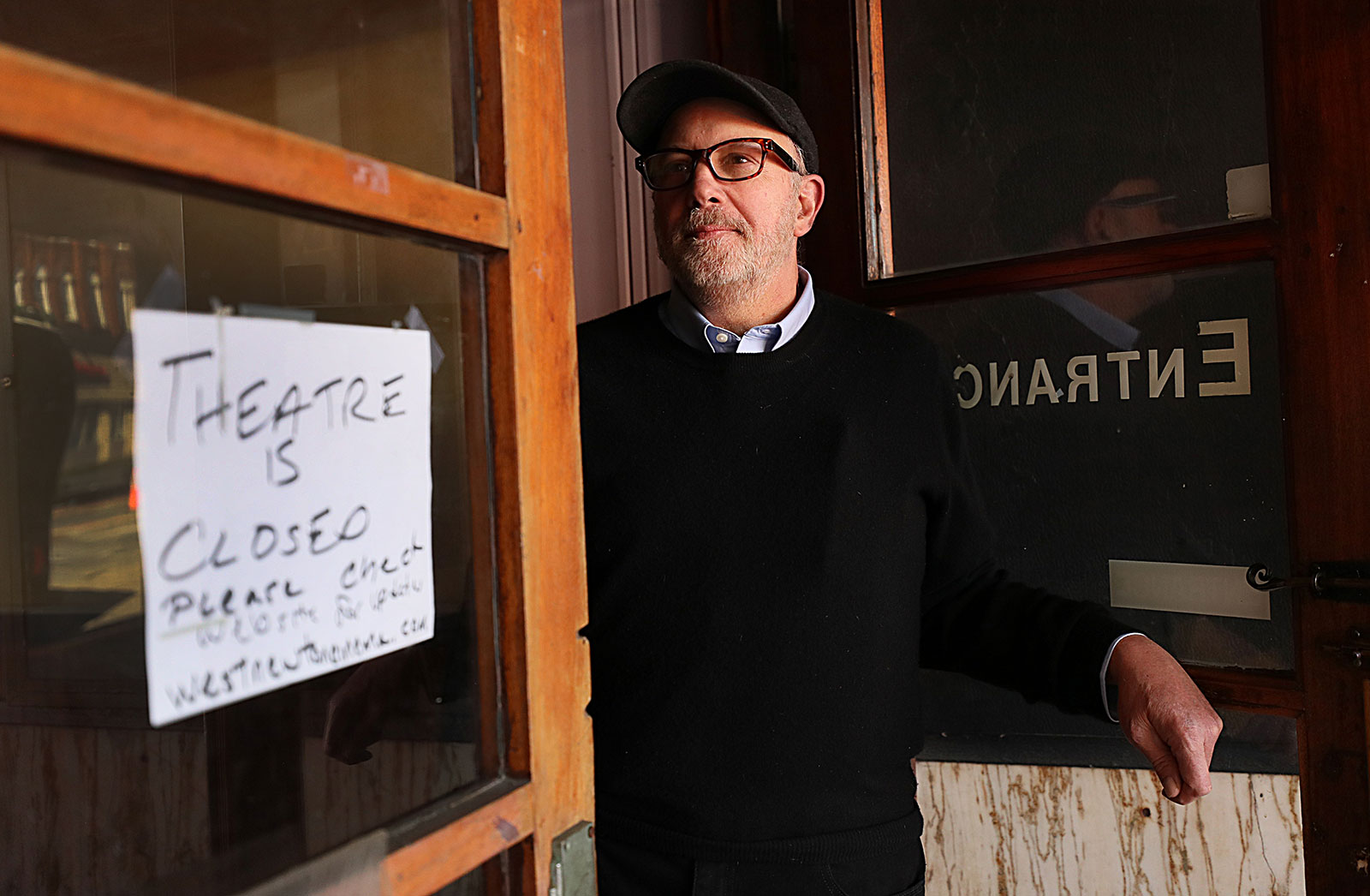 David Bramante, the owner of West Newton Theatre in Newton, Massachusetts, stands in the doorway of the theater on March 27. Bramante had to close the theatre due to the coronavirus pandemic.