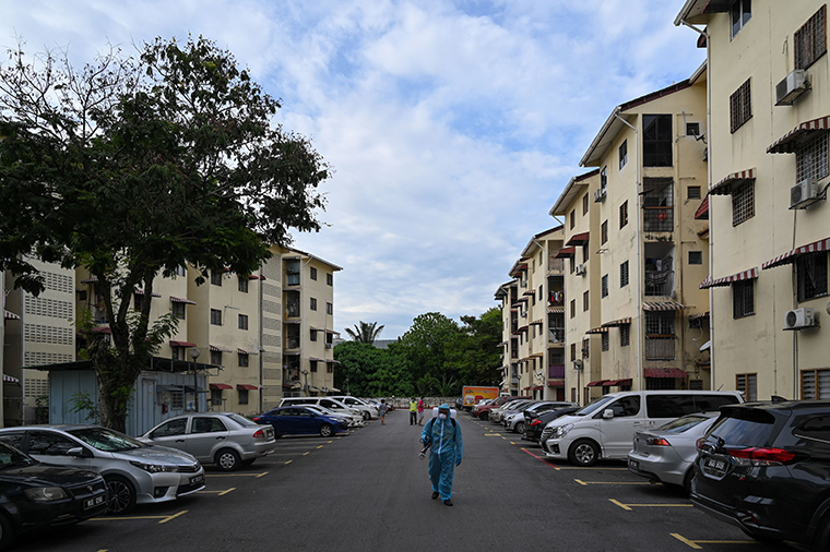 A city council volunteer worker in protective gear walks before spraying disinfectant, amid the COVID-19 coronavirus pandemic, next to apartment buildings in Kuala Lumpur on October 26, 2020.