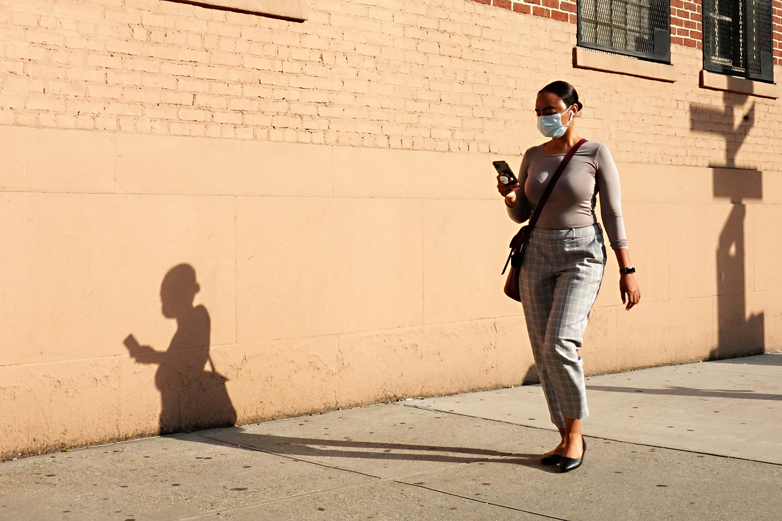 A woman wearing a protective mask walks while looking at a cellphone on August 6, in New York City.