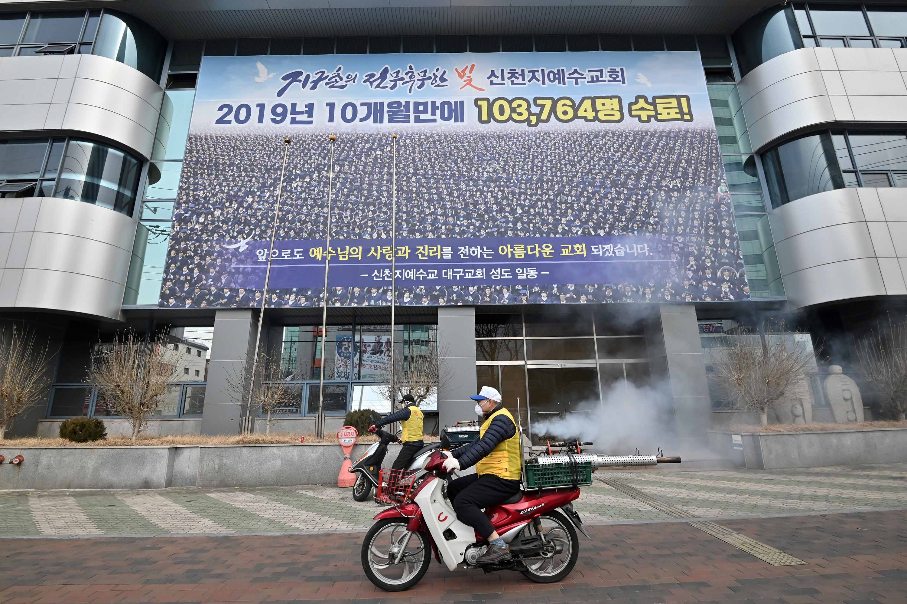 South Korean health officials spray disinfectant in front of the Daegu branch of the Shincheonji Church of Jesus in Daegu, South Korea, on February 21.