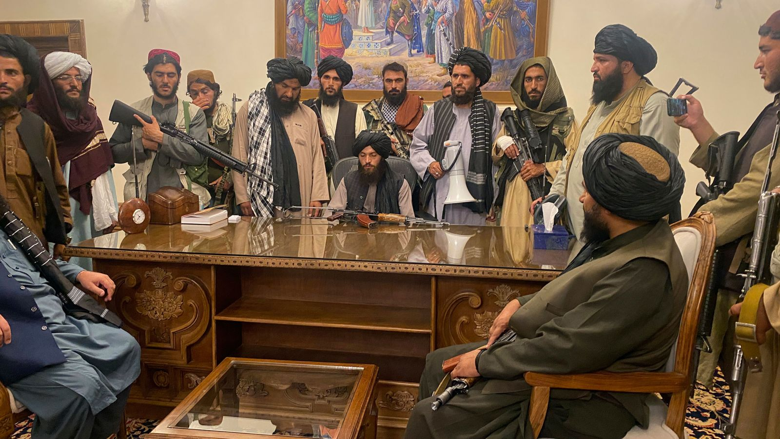 Taliban fighters sit inside the presidential palace in Kabul on August 15.