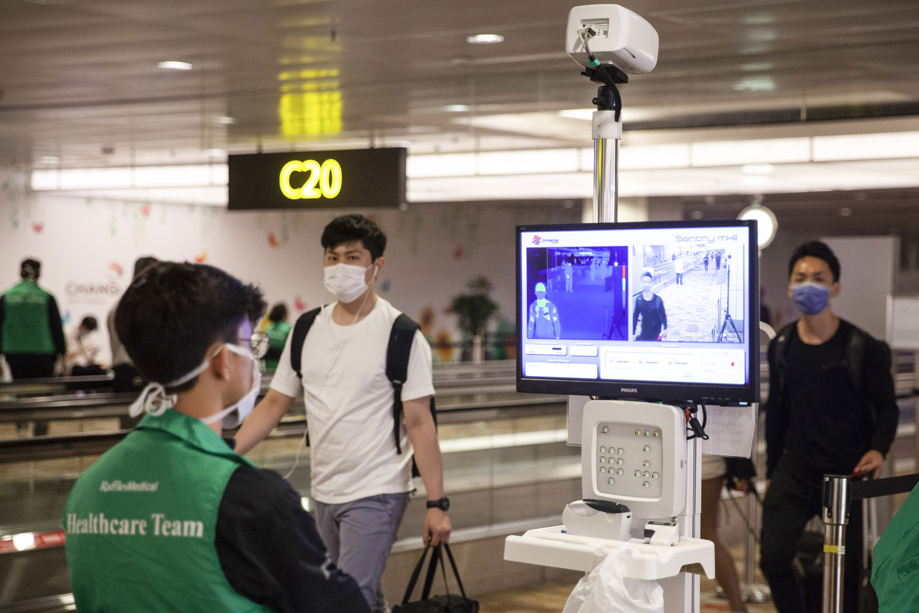 Passengers' temperatures are checked as travelers pass through Changi Airport in Singapore on March 11.