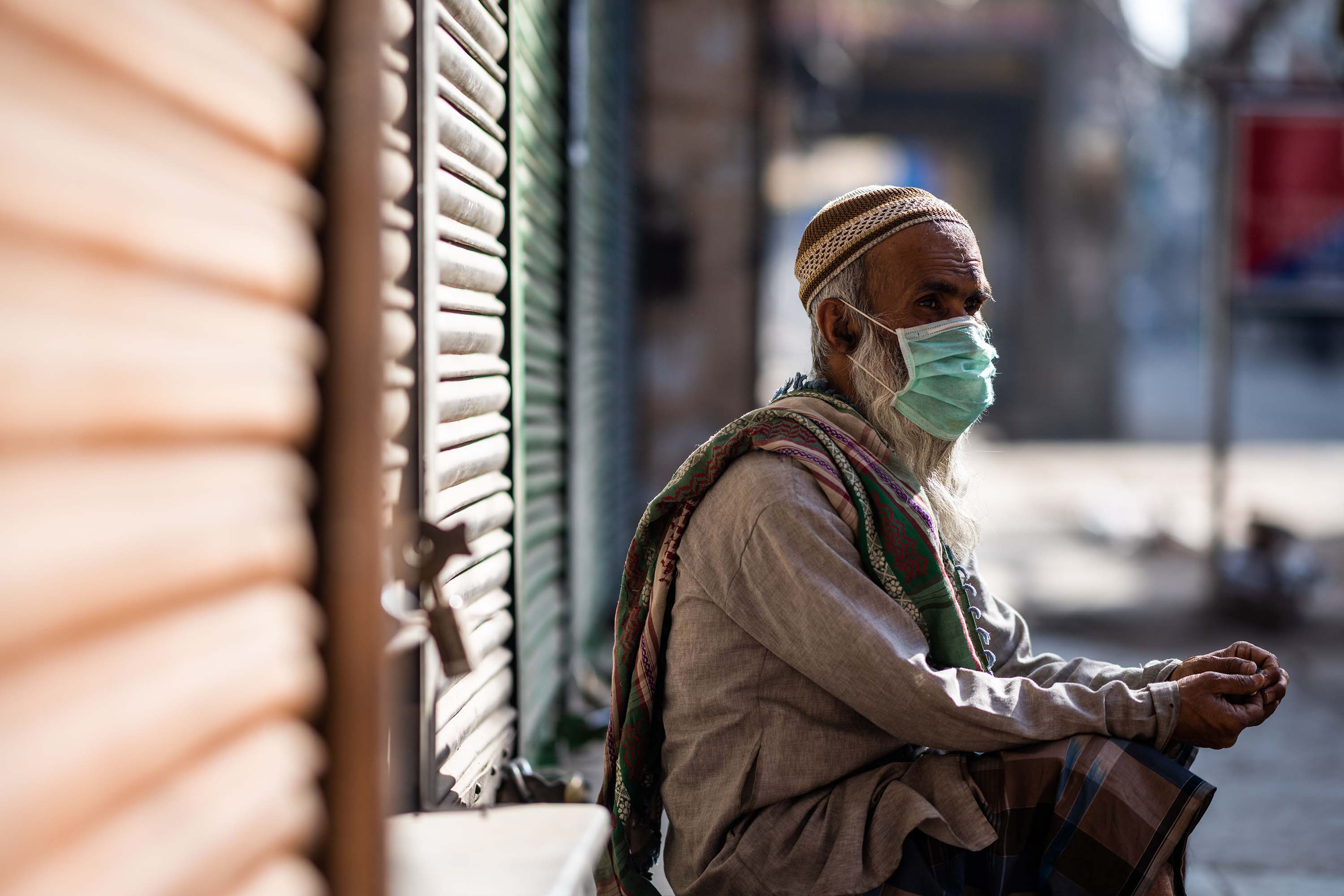 A man wearing a face mask sits in front of a closed shop during a government-imposed nationwide lockdown in New Delhi, India, on April 6.