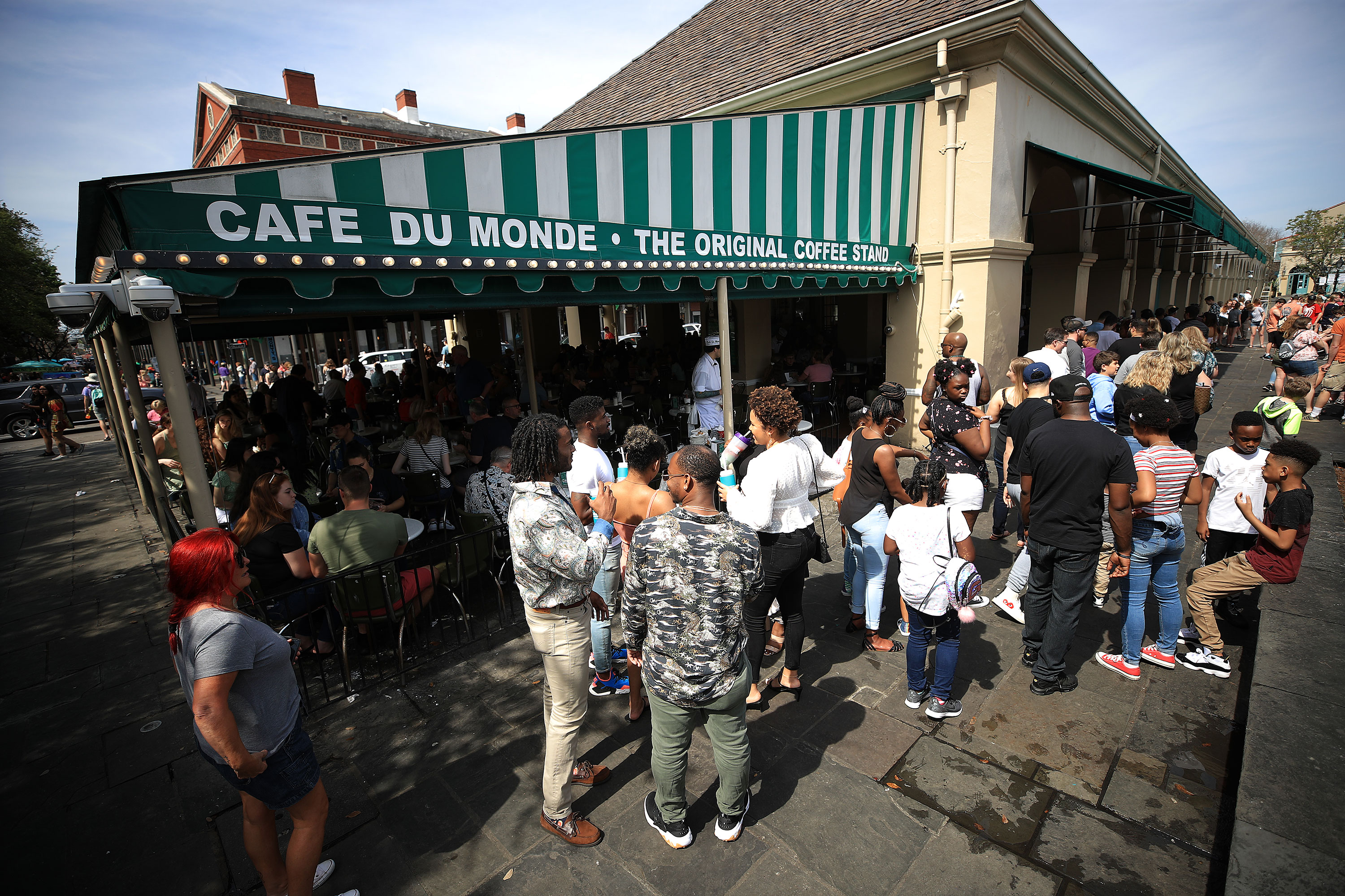 People wait in line outside the renowned Cafe Du Monde in the French Quarter of New Orleans on Sunday.