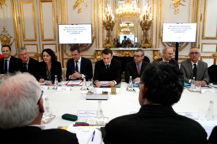 French President Emmanuel Macron, center, and Health minister Olivier Veran, centre left, hold a meeting with with researchers and scientists about the COVID-19 outbreak, at the Elysee Palace in Paris, France, Thursday, March 5.