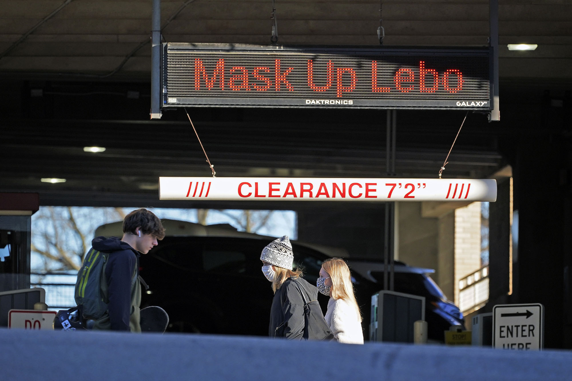 Pedestrians walk past a sign on a parking garage in Mount Lebanon, Pennslyvania, reminding people to wear a mask, on Wednesday, November 18.
