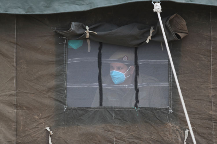An Indian policeman looks out from a tent at an isolation ward set up for possible coronavirus patients in Jammu, India, on Wednesday, March 11.