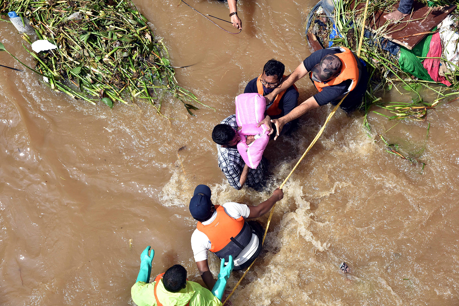 National Disaster Response Force personnel rescue a baby and her family from a waterlogged house at Hafiz Baba Nagar at Hyderabad in India's southern state of Telangana, on October 18.