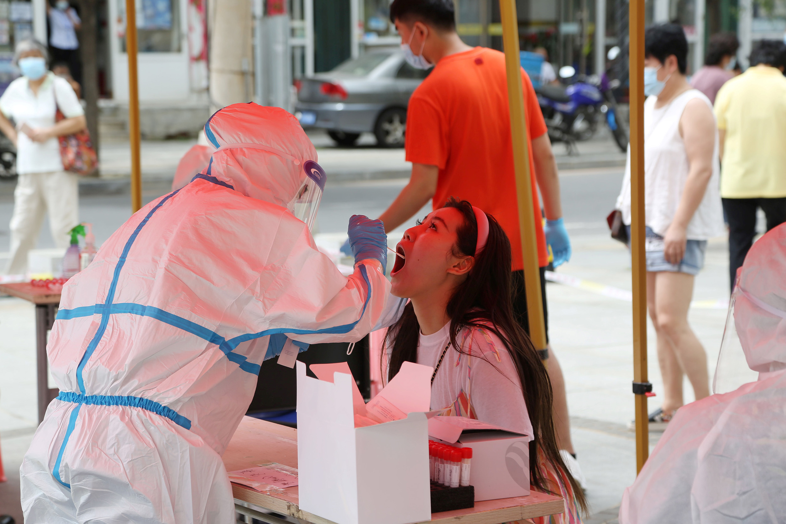 A health worker takes a swab sample test for Covid-19 at a makeshift testing center in Dalian, China on July 27.