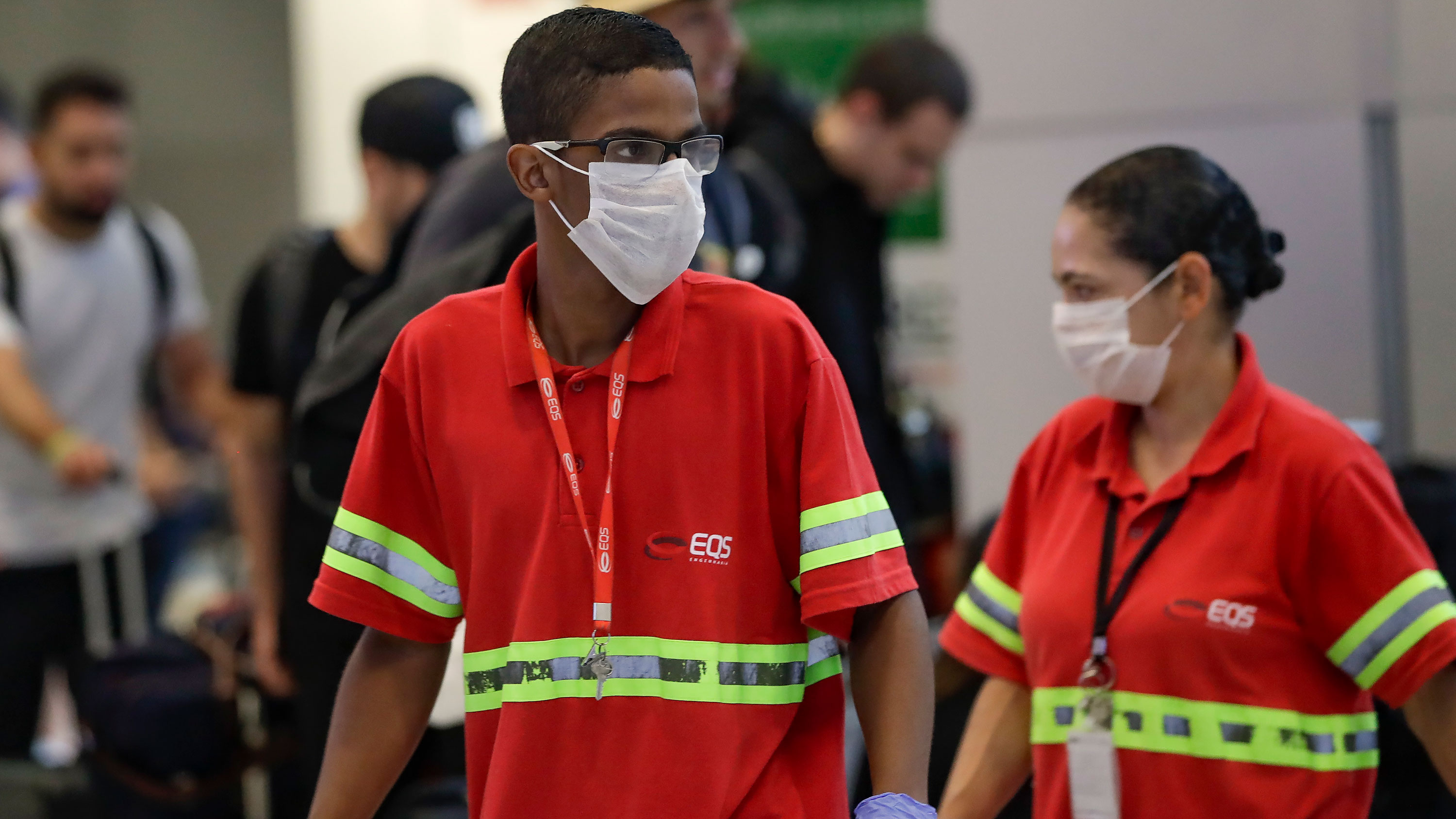 Airport employees wear masks as they work at the Sao Paulo International Airport in Sao Paulo, Brazil, on Wednesday, February 26.