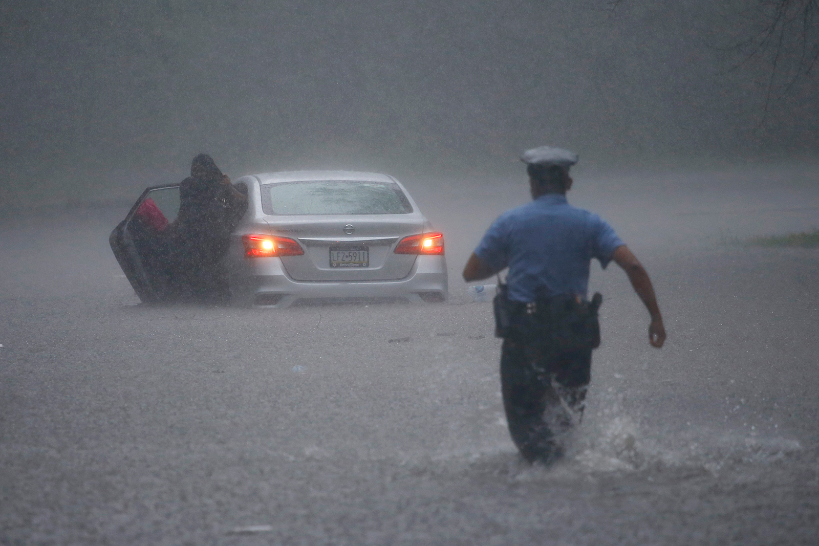 A Philadelphia police officer rushes to help a stranded motorist during Tropical Storm Isaias, on Tuesday, August 4, in Philadelphia.