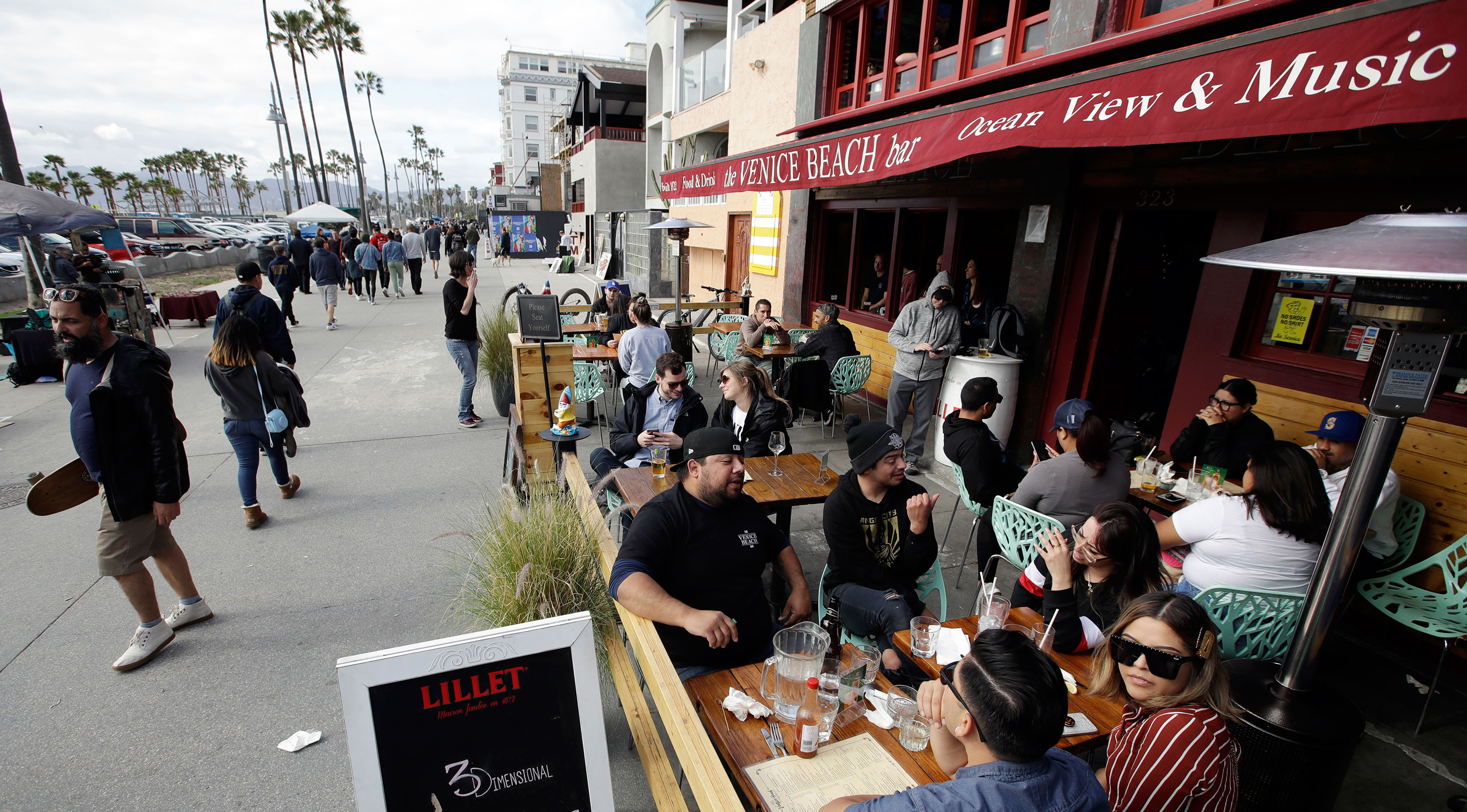 Patrons sit outside a bar along the Venice Beach Boardwalk on Sunday in Los Angeles.