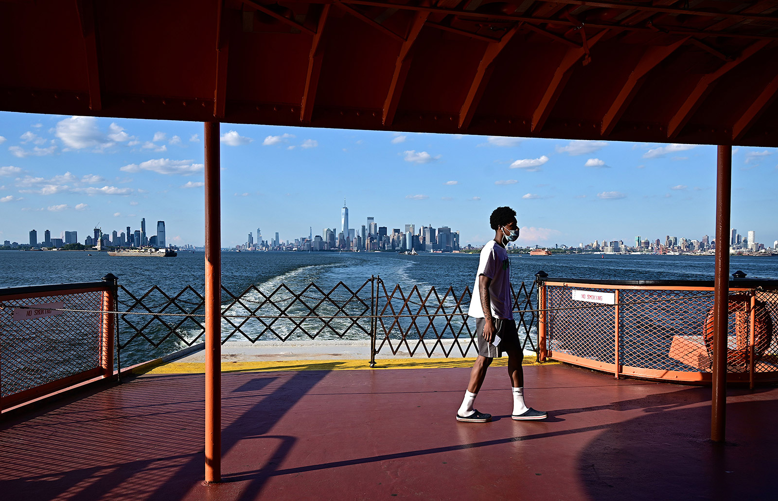 A man stands on the deck of a Staten Island ferry in front of the Manhattan skyline in New York on July 13.