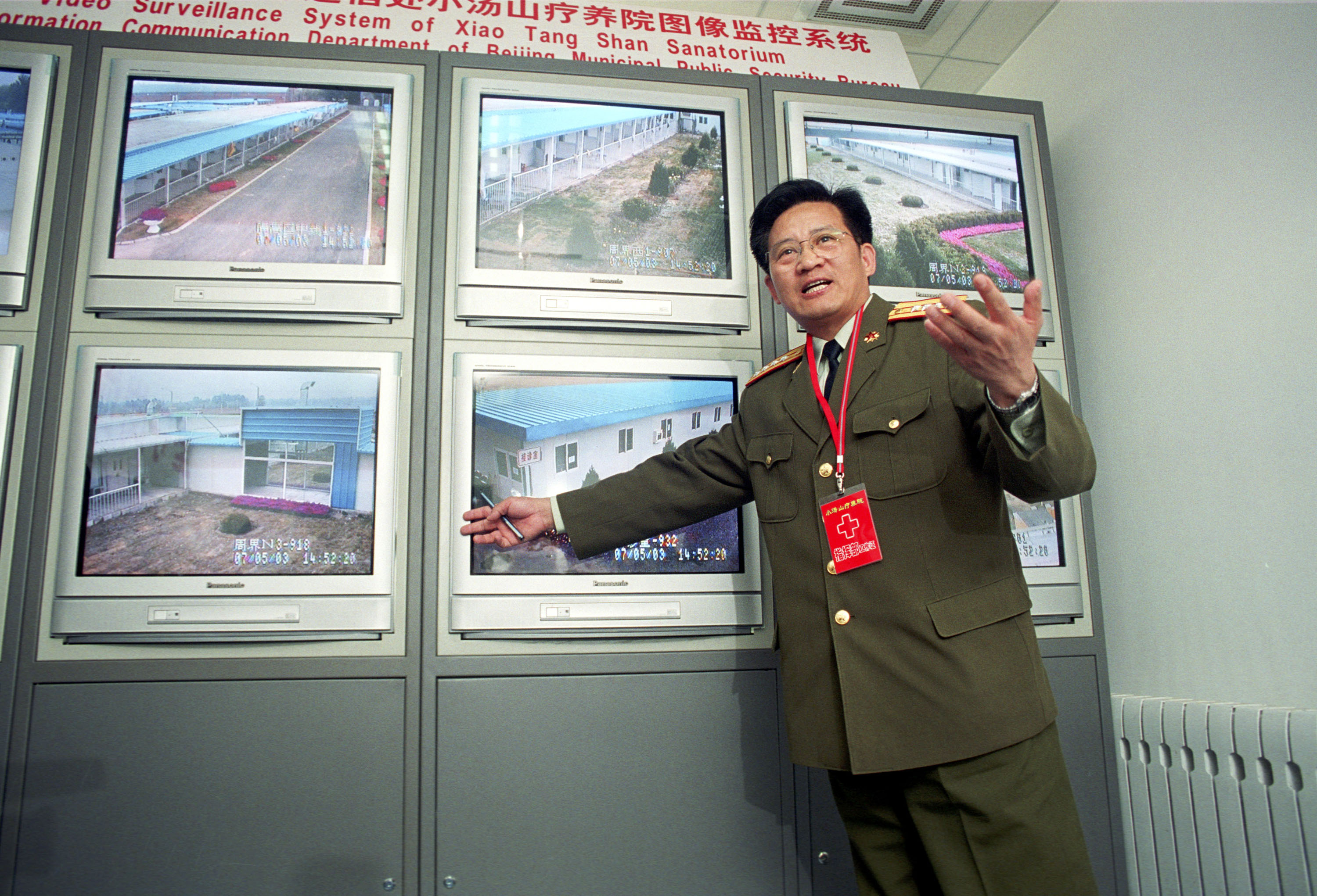 A military official explains the surveillance system of a newly built 1,000 bed SARS hospital to journalists on May 7, 2003 in Xiaotangshan, near Beijing, China.