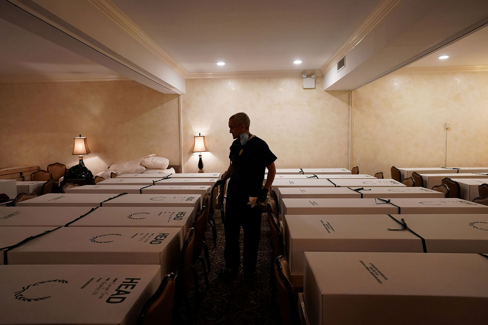 Funeral Director Omar Rodriguez walks by caskets at Gerard J. Neufeld funeral home in Queens, New York, on April 26.