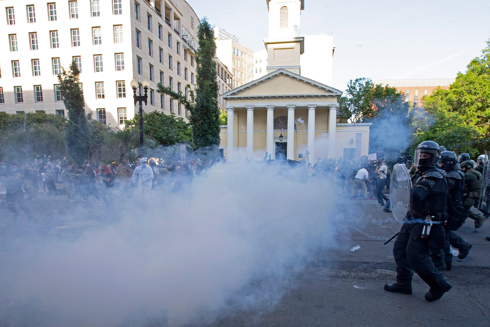 Police officers wearing riot gear push back demonstrators shooting tear gas next to St. John's Episcopal Church outside of the White House in Washington, on June 1.