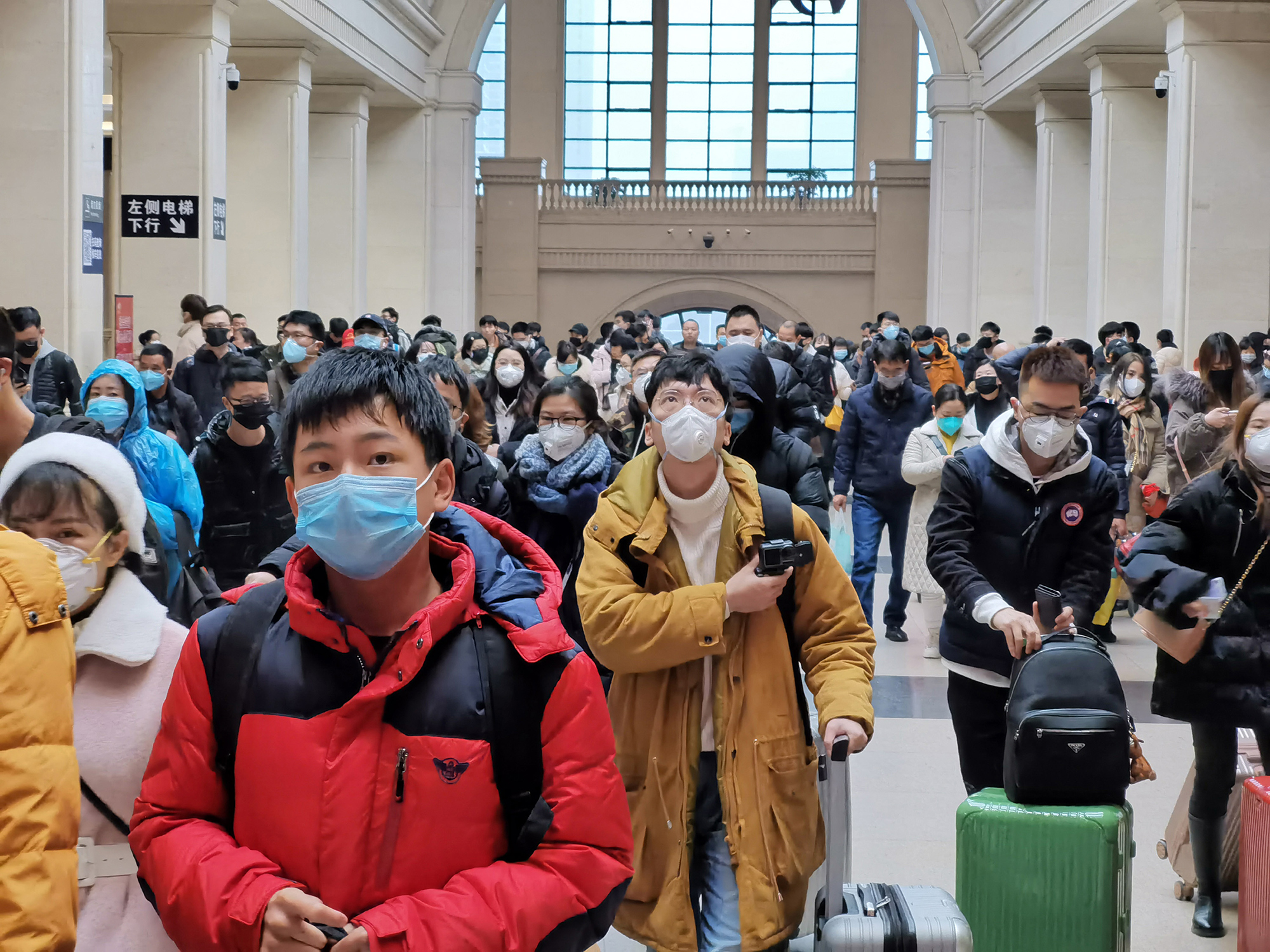 People wear face masks as they wait at Hankou Railway Station on Wednesday in Wuhan, China.