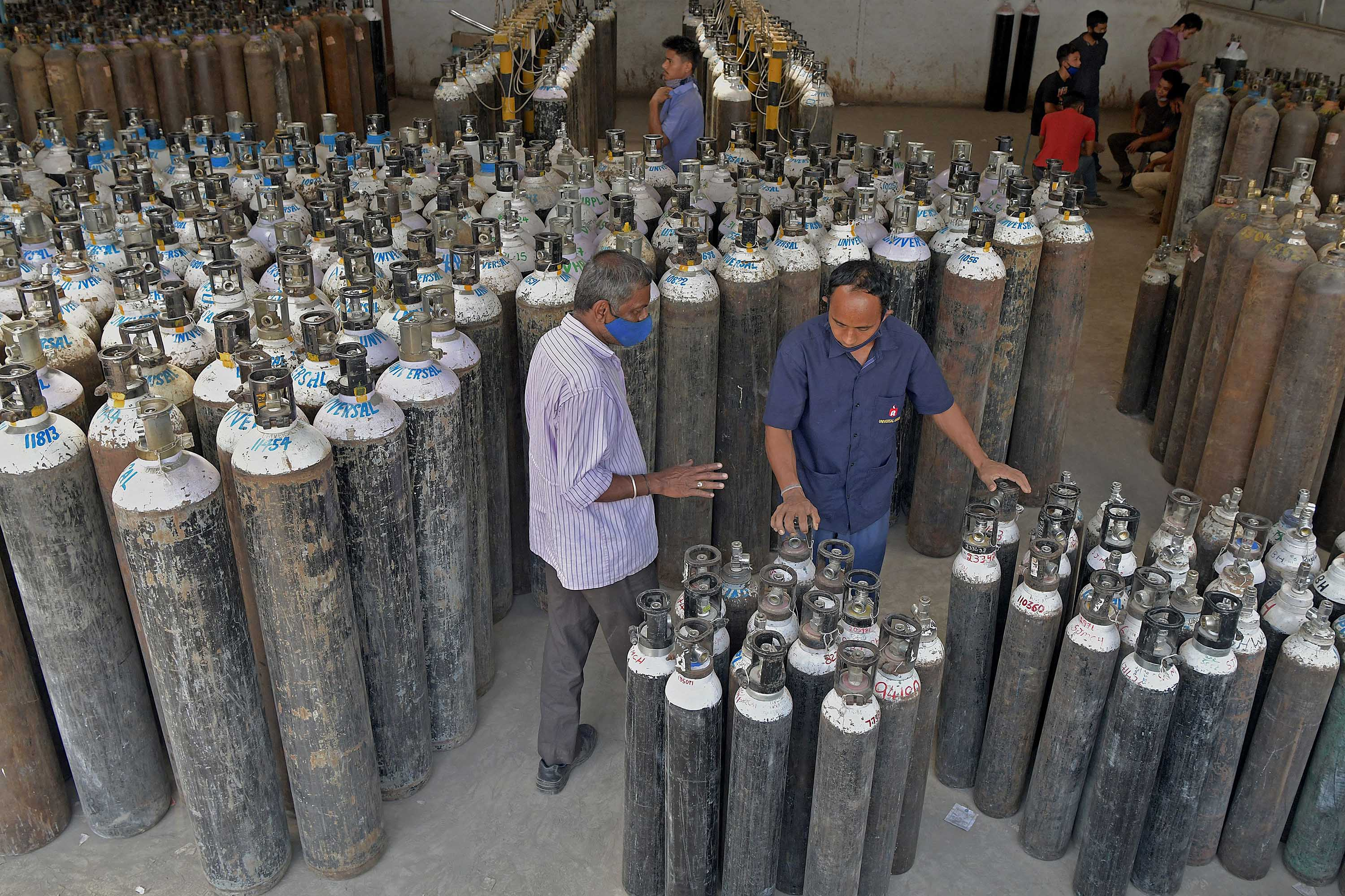 Workers are seen sorting oxygen cylinders for distribution to hospitals in Bangalore, India, on April 19, where they will be used to treat Covid-19 patients.