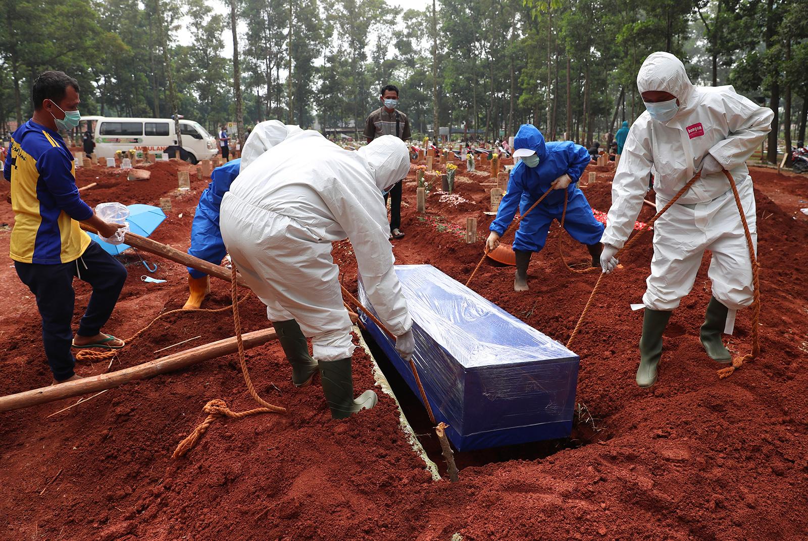 Des travailleurs en tenue de protection descendent le cercueil d'une victime de Covid-19 dans une tombe pour l'enterrer au cimetière Cipenjo à Bogor, dans l'ouest de Java, en Indonésie, le mercredi 14 juillet.