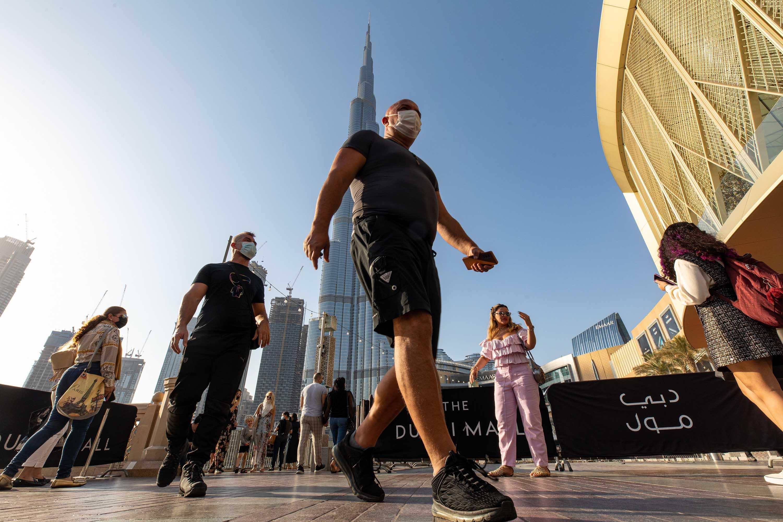 Tourists wearing protective masks walk near the Dubai Mall and the Burj Khalifa skyscraper in Dubai, United Arab Emirates, on Wednesday, January 27.