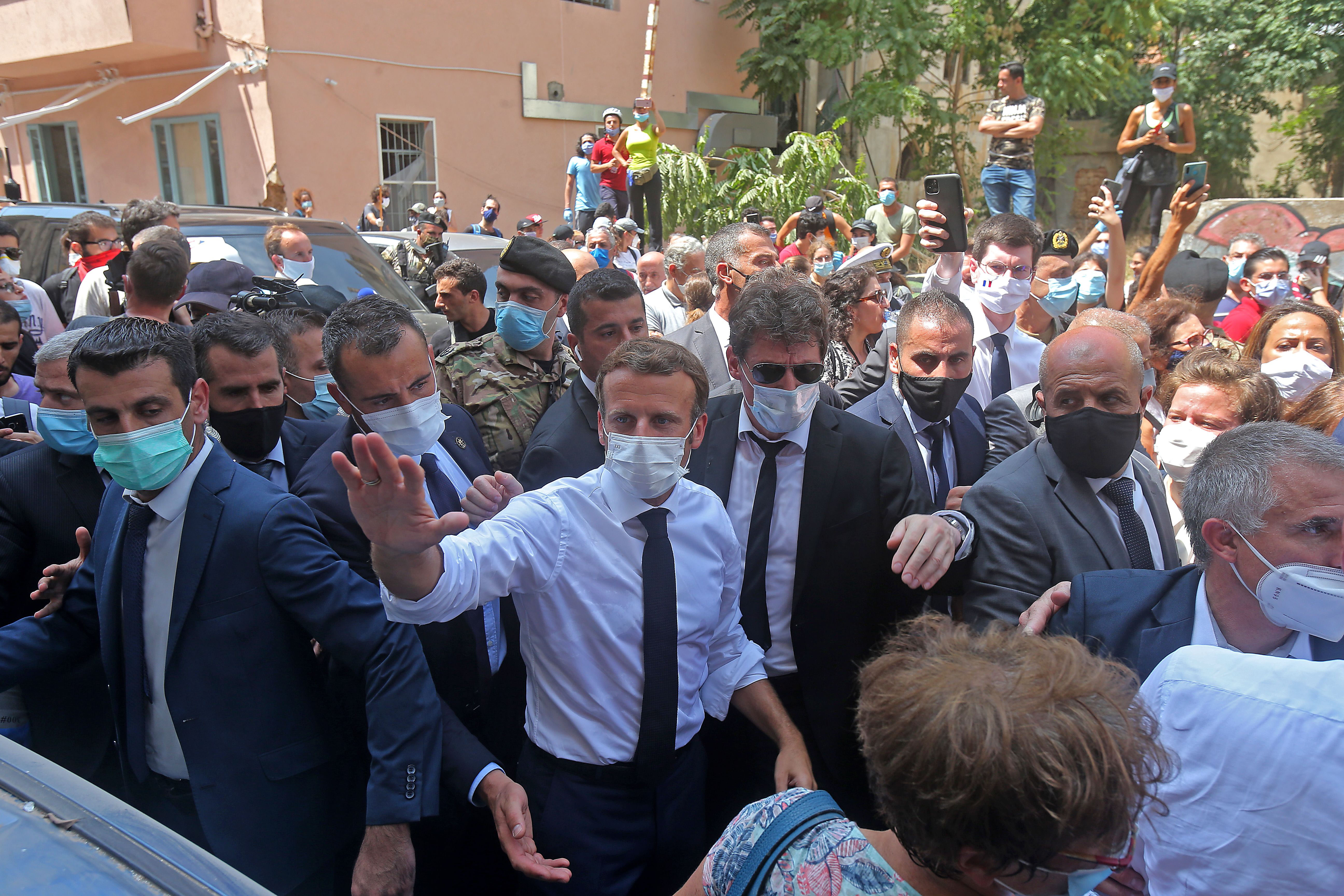 French President Emmanuel Macron, in the white shirt, greets people on August 6 as he visits the Gemmayzeh neighborhood in Beirut, Lebanon.