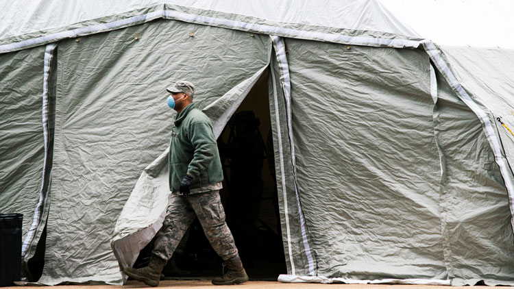 An Air Force member exits a tent builded as makeshift morgue outside of Bellevue Hospital on March 25, in New York City.