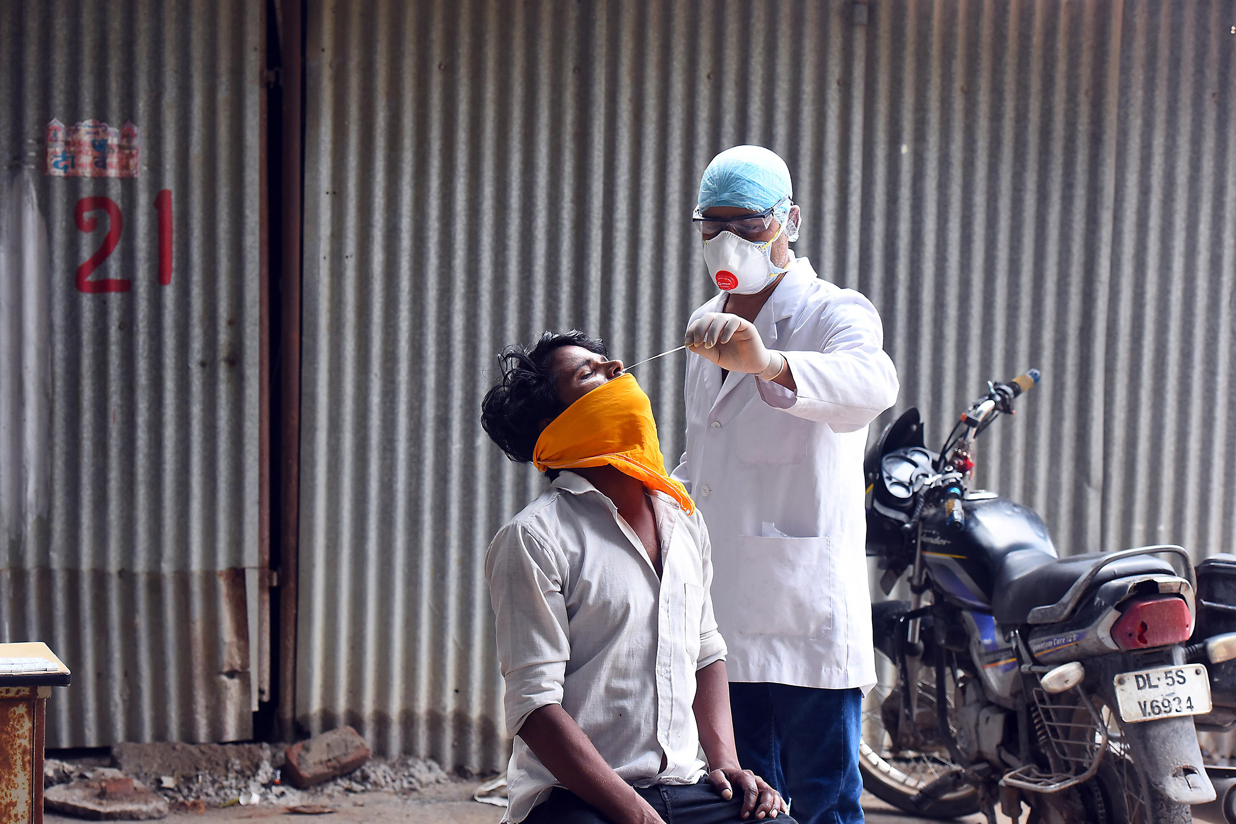 A health worker takes a swab sample from a man for coronavirus testing on September 6, in New Delhi, India.