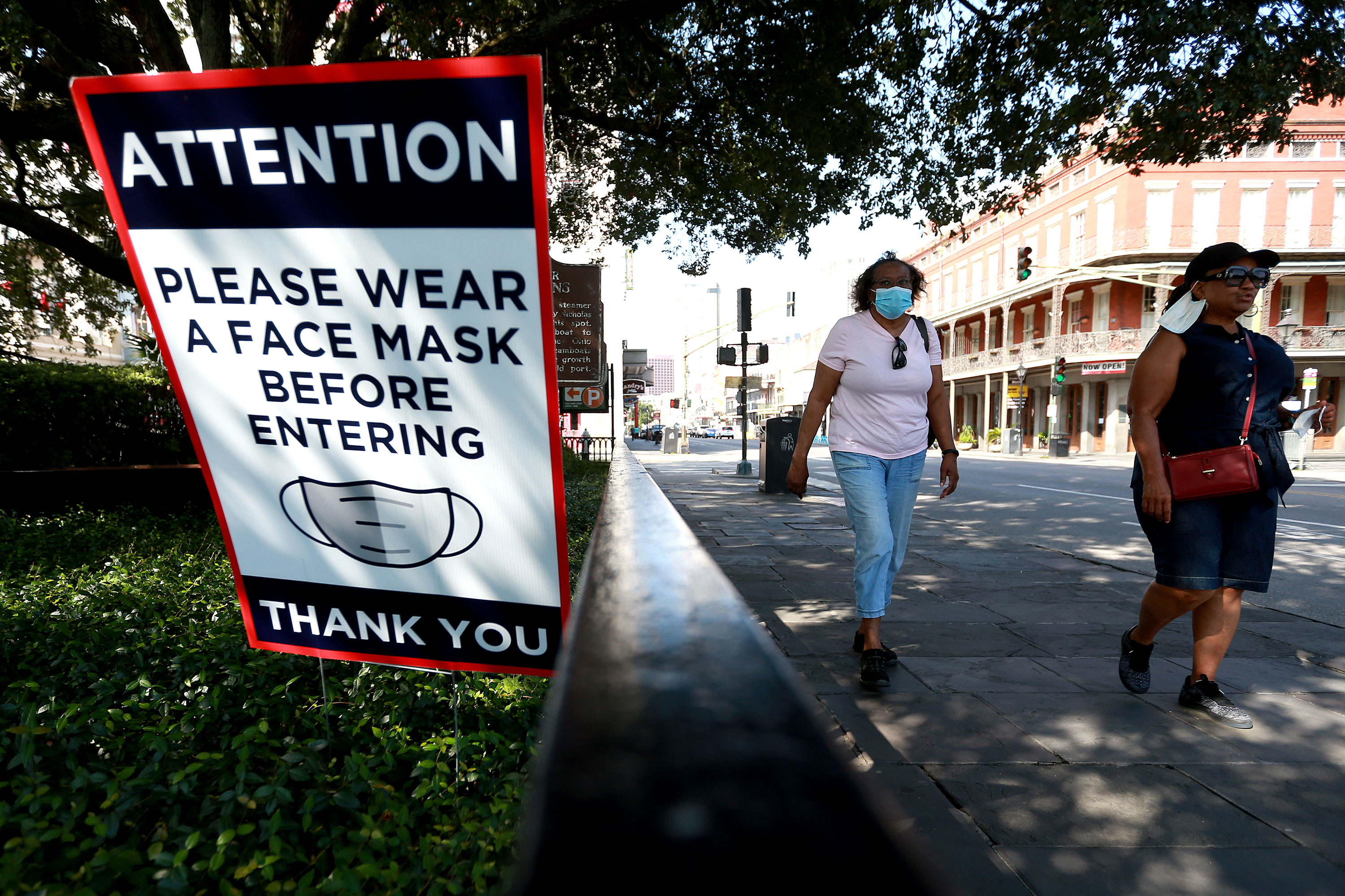 People walk past face mask signs along Decatur Street in the French Quarter of New Orleans on July 14.