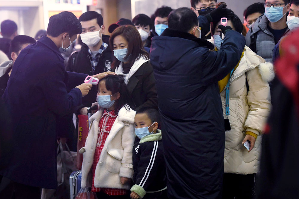 Workers use infrared thermometers to check the temperature of passengers arriving from Wuhan at a train station in Hangzhou on Thursday, January 23.