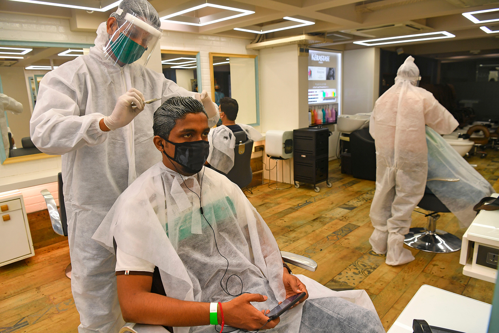 Staff at Shiva's Signature hair salon wearing Personal Protective Equipment  suits and face shields attend customers after personal grooming services were allowed to resume following relaxation of lockdown norms amidst Covid-19 coronavirus pandemic, in Mumbai on June 28, 2020. - India now has more than 500,000 confirmed coronavirus cases, according to government figures released on June 27 that showed a record daily leap of 18,500 new infections. (Photo by INDRANIL MUKHERJEE / AFP) (Photo by INDRANIL MUKHERJEE/AFP via Getty Images)