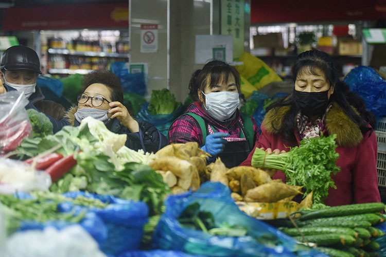 People buy vegetables in Hangzhou in China's eastern Zhejiang province on February 9.