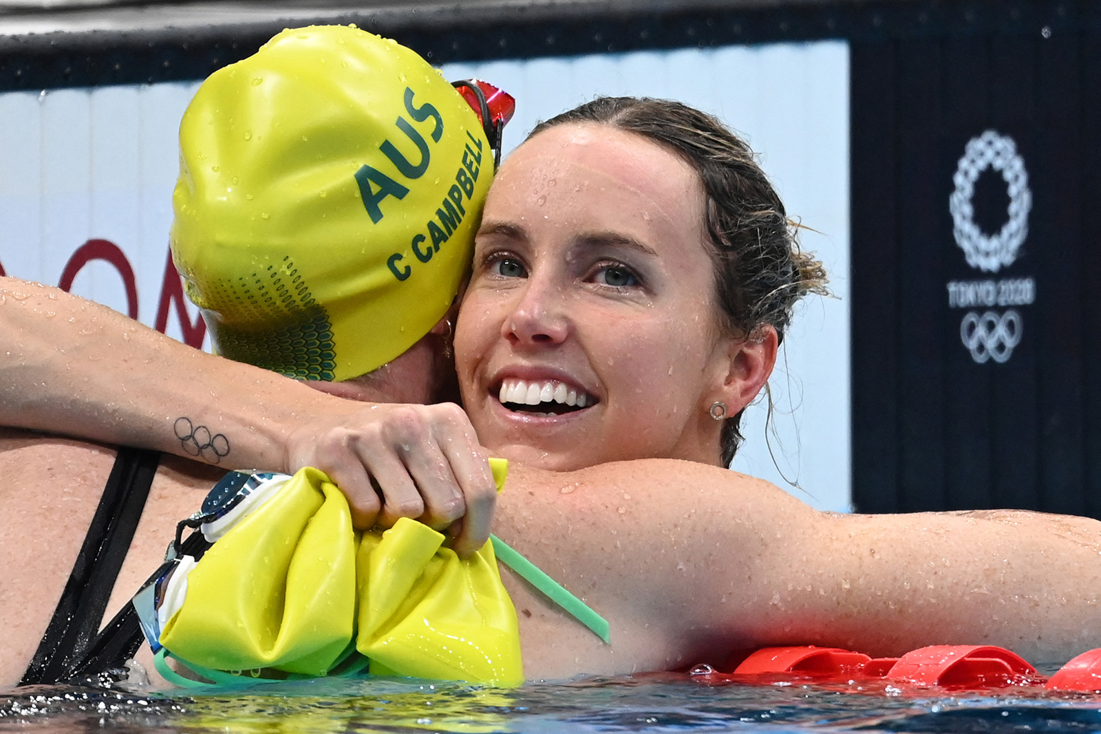 Australia's Emma McKeon celebrates with Australia's Cate Campbell after winning the final of the women's 100-meter freestyle swimming event and setting an Olympic Record on Friday.