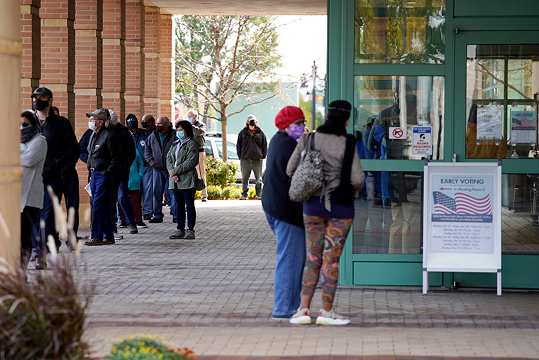 People wait in line during early voting at Des Plaines Public Library in Des Plaines, Illinois, Wednesday, October 21.