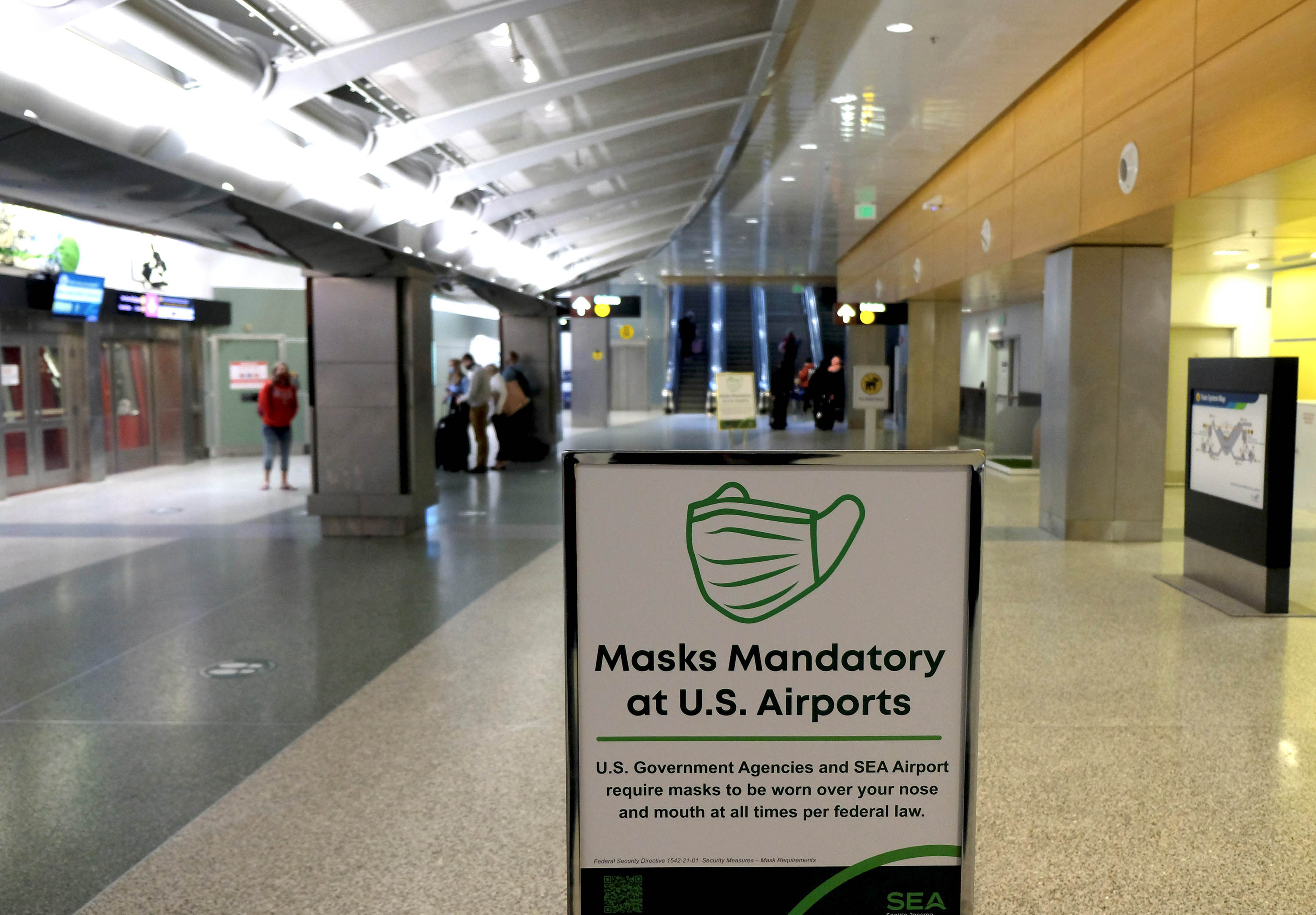 A sign gives notice of mandatory requirements for wearing masks, at an airport in Seattle, Washington, on March 14.