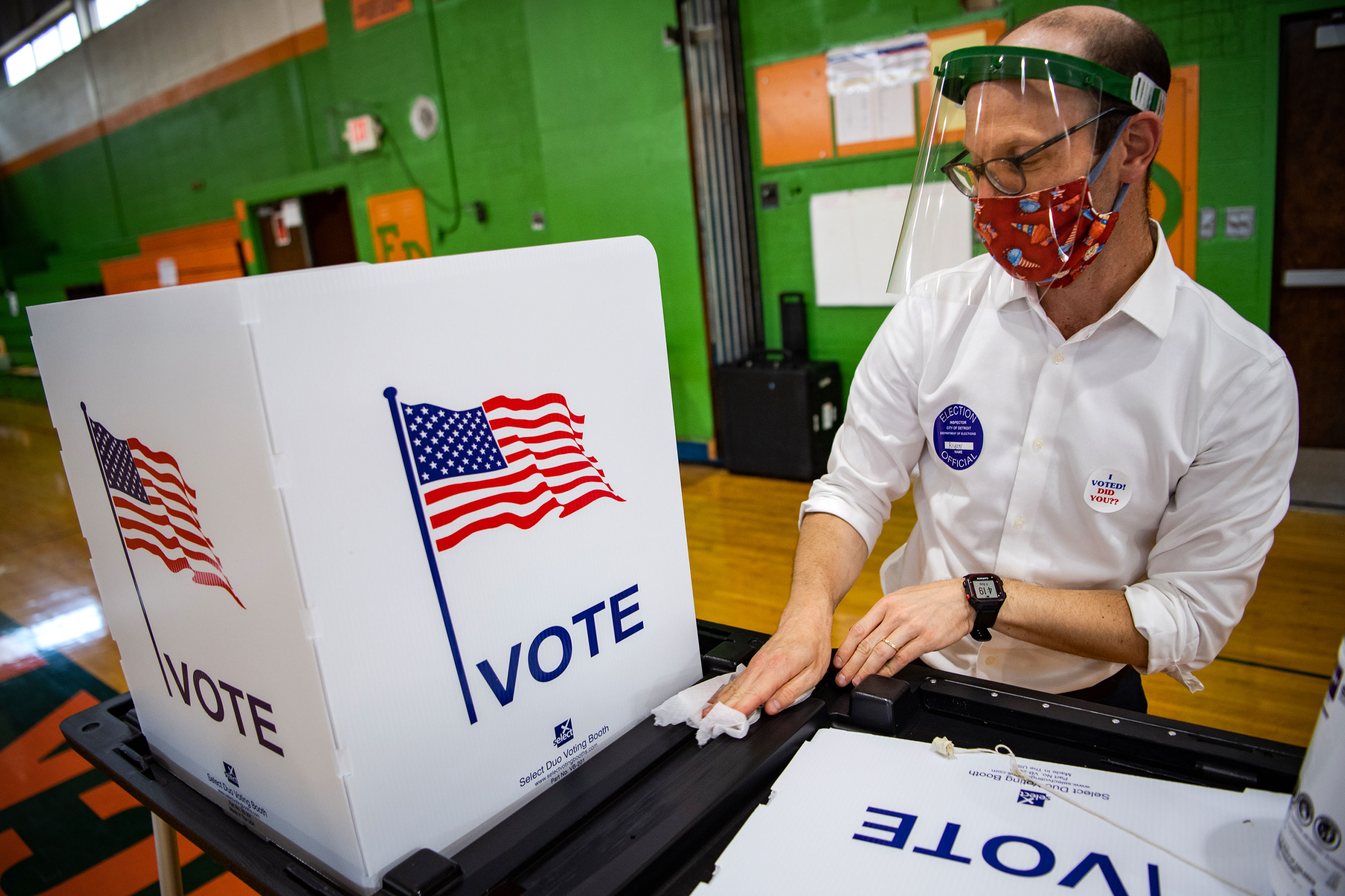A volunteer disinfects a voting booth at a polling station during the Michigan Primary on August 4 in Detroit, Michigan.