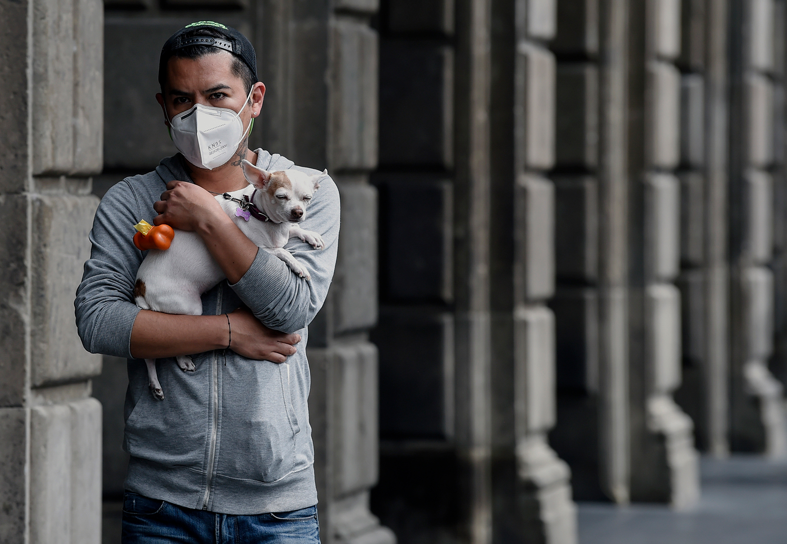 A man wearing a face mask holds his dog at downtown Mexico City on July 6.