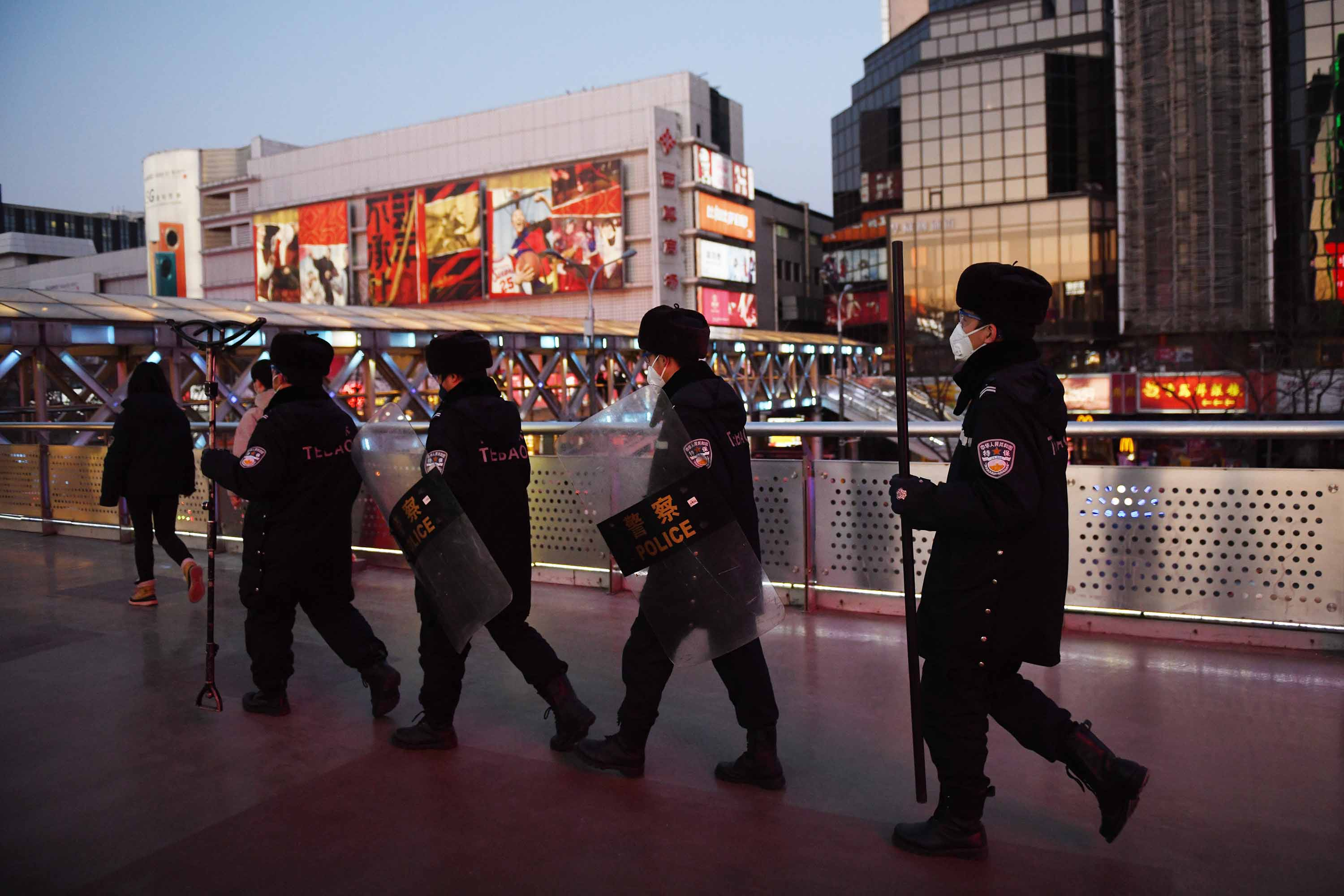 Security guards wearing protective masks patrol a shopping area in Beijing on Monday.