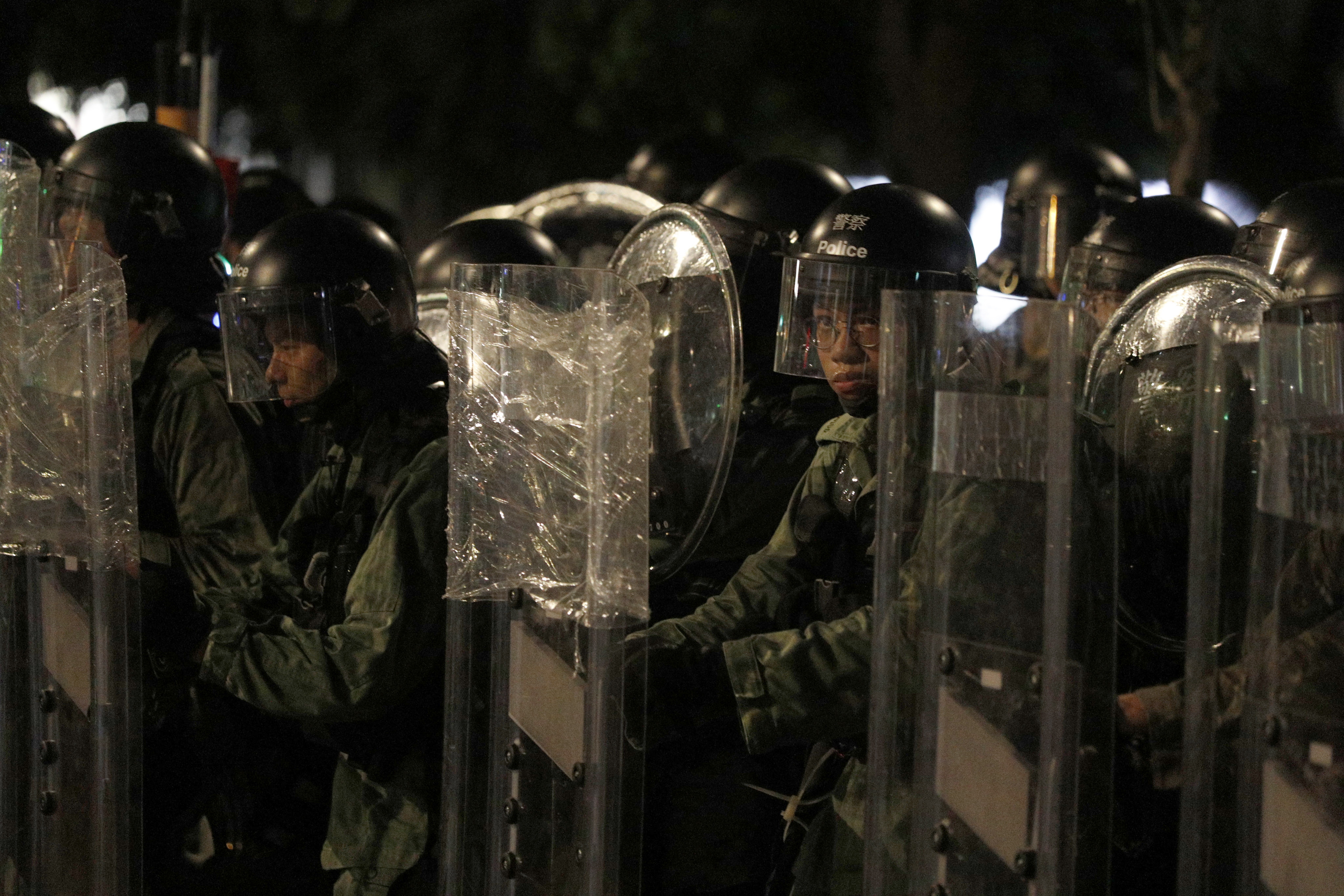 Riot police stand behind shields as they face off protesters in Yuen LongSaturday.