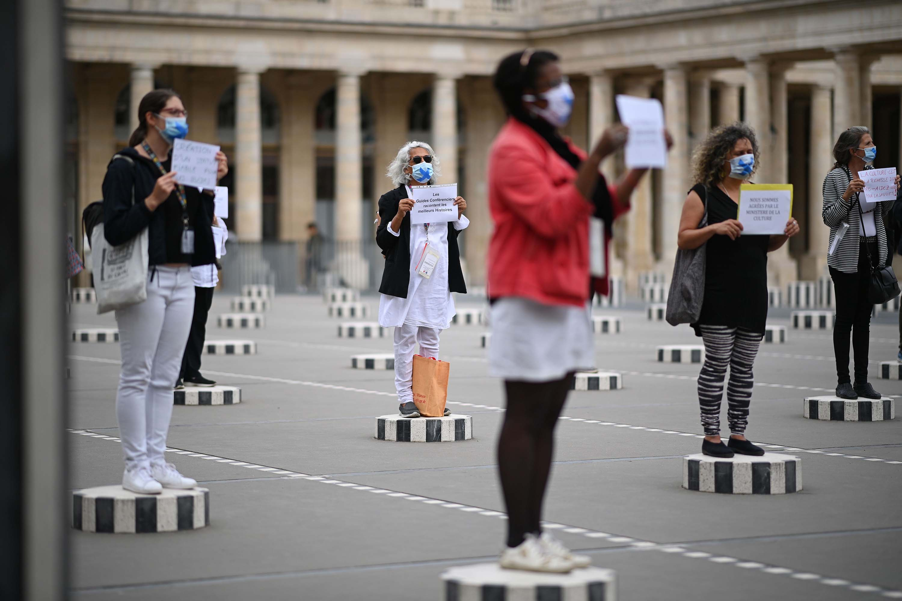 Tour guides protest working conditions due to the novel coronavirus disease outbreak, as they stand on columns of an art installation by French artist Daniel Buren, at the Palais Royal gardens in Paris, on July 16.